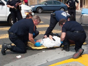 Police and paramedics ready the crash victim for transportation to the hospital.
