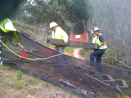 Workers lift a 100-pound box into place to create another tread in the stairway of the trail.