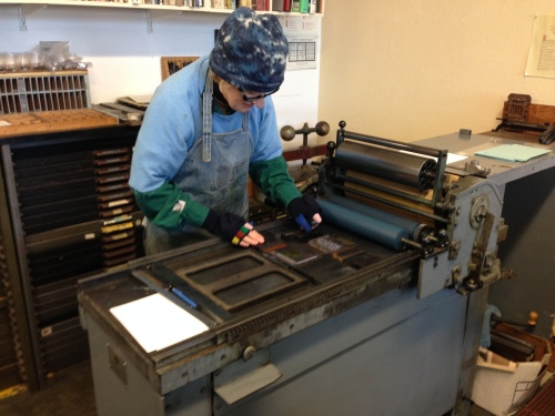 Mary inspecting type, after it has been secured into place in the printer bed.