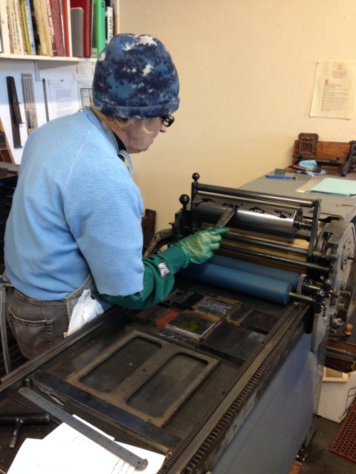 Mary inspecting rollers after they have been inked.