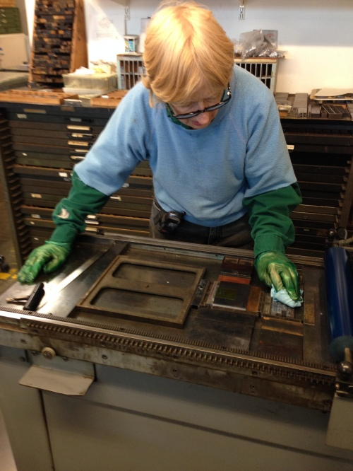 Mary cleaning the type, after her printing run is completed.