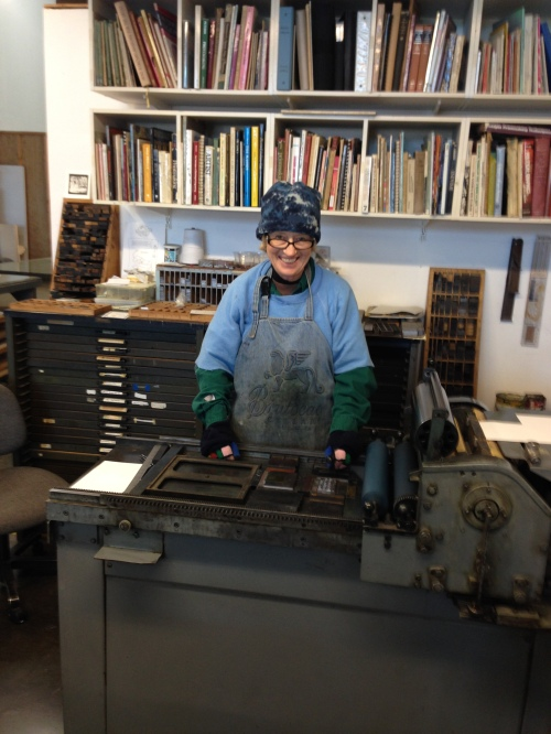 Mary Huizinga standing at her letterpress printer.