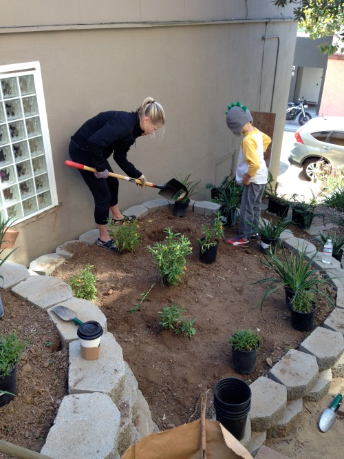 Diana Scearce does the digging while her son, Miles supervises.