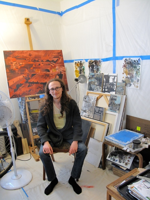 - Robbie Sugg sitting in his San Jose studio. Photo by John Landry