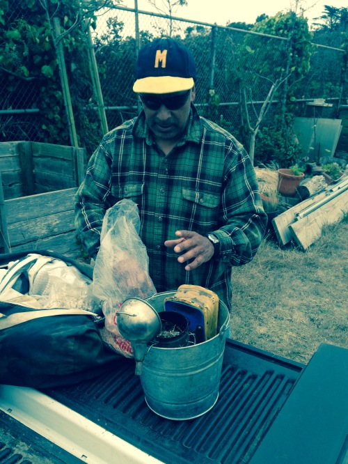 Fernado Aguilar, wearing his McAteer High School baseball cap, preparing to stoke his smoker, which he uses to calm his bees.